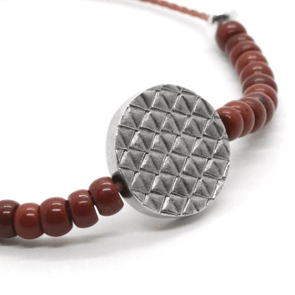 Ein Xango-Armband, mit einem Mittelstück aus 925er Silber und dem Rest der Kette aus kleinen roten Jaspisperlen.