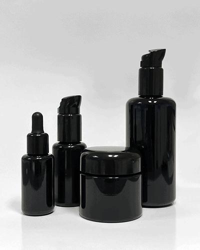 3 flacons de tailles diverses ainsi qu'un petit pot, tous en verre Miron violet résistant aux UVs.